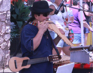 A vendor demonstrates the sounds his instruments can make to passerby at the festival.